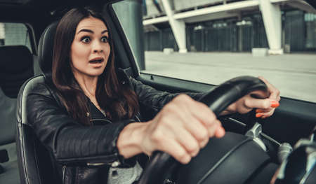 Beautiful girl in leather jacket is looking forward with widely open eyes and feeling shock while driving a car
