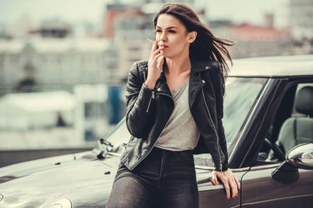 Beautiful girl in leather jacket is smoking and looking away while leaning on her car