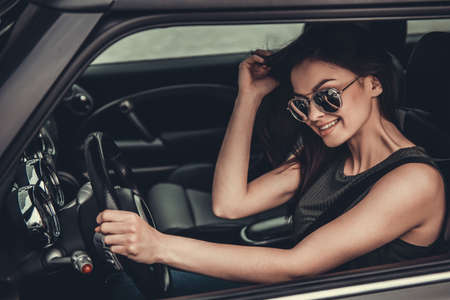 Beautiful girl in sun glasses is smiling while driving a car Imagens