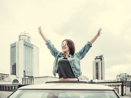 Beautiful girl in sun glasses is sticking out the sunroof and smiling while traveling by car