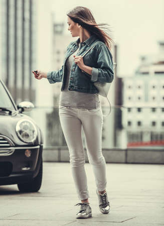 Full length image of beautiful girl in jean jacket locking her car