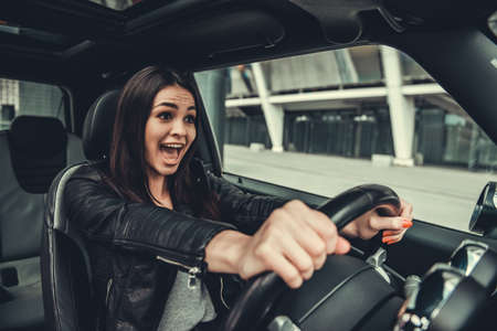 Beautiful girl in leather jacket is screaming while driving a car