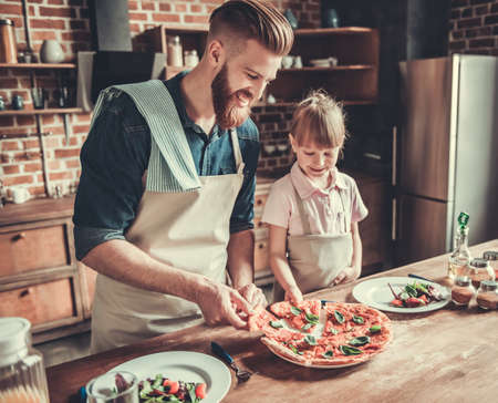 Cute little girl and her handsome bearded dad in aprons are taking pieces of just cooked pizza and smiling