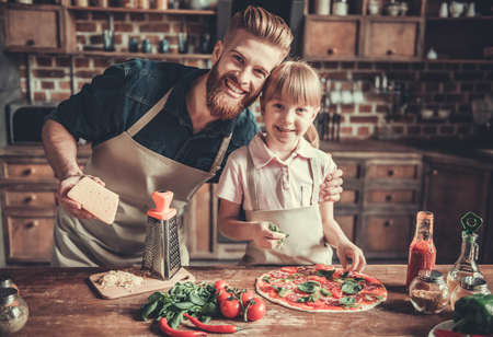 Cute little girl and her handsome bearded dad in aprons are looking at camera and smiling while cooking pizza in kitchen
