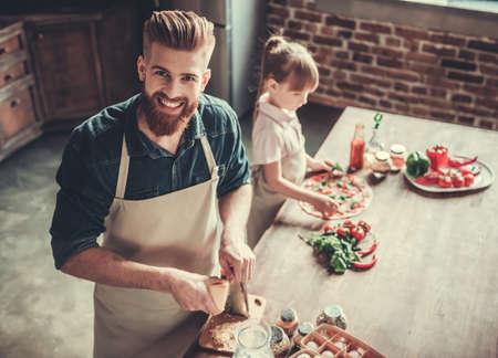 Leuk klein meisje en haar knappe gebaarde vader in schorten glimlachen tijdens het koken van pizza in de keuken