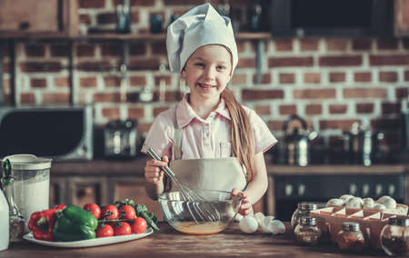 Cute little girl in chefs hat and apron is whisking eggs, looking at camera and smiling while cooking in kitchen