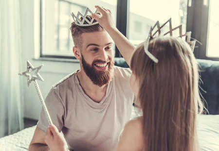 Cute little girl and her handsome bearded dad in crowns are smiling while playing in her room Archivio Fotografico
