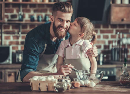Cute little girl and her handsome bearded dad in aprons are whisking eggs while cooking in kitchen. Daughter is kissing her daddy in cheek Stock Photo