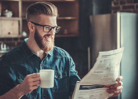 resting: Handsome bearded young man is drinking coffee, reading a newspaper and smiling while resting in kitchen