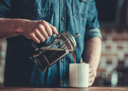 Cropped image of young man pouring coffee into the cup while standing in kitchen Stok Fotoğraf - 82314659