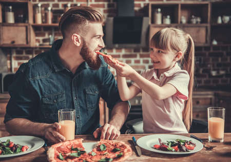 Cute little girl and her handsome bearded dad are smiling while drinking juice and eating pizza in kitchen