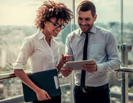 Handsome businessman and beautiful Afro American businesswoman are using digital tablet and smiling while standing on balcony of the office building