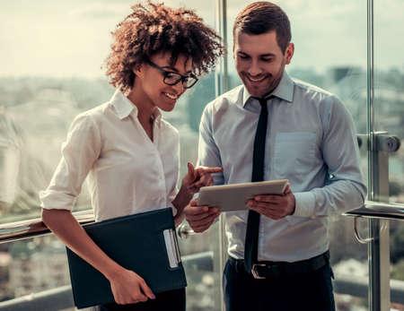 ハンサムな実業家と美しいアフロ アメリカ実業家デジタル タブレットを使用しているし、オフィスの建物のバルコニーに立って笑顔