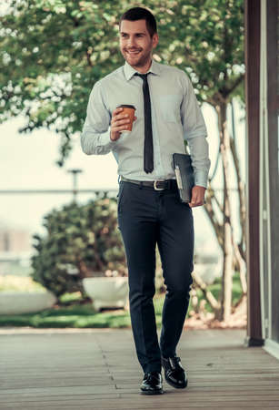 Full length portrait of handsome businessman holding a folder, drinking coffee and smiling while walking outdoors