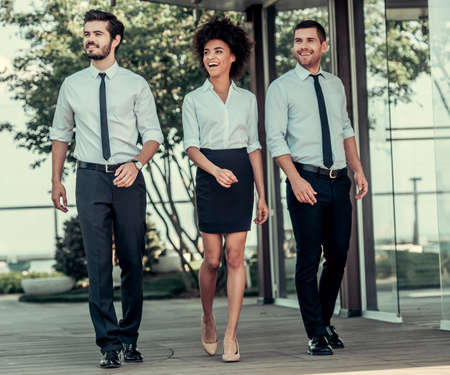 Full length portrait of beautiful business people smiling while walking outdoors