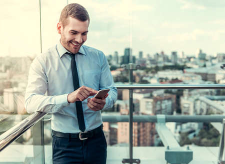 Handsome businessman is using a smart phone and smiling while resting on balcony of the office building