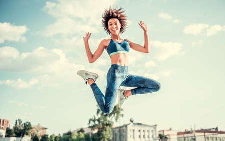 スポーツ ウエアで美しいアフロ アメリカン ガールのカメラ目線と都市背景でジャンプしながら笑みを浮かべて