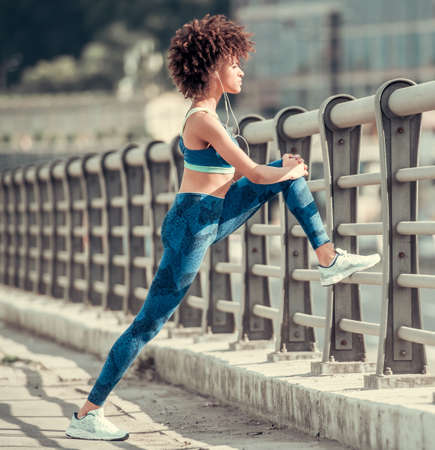 Mooie Afro-Amerikaanse meid in sportkleding en oortelefoons strekt zich uit voor de morgenloop