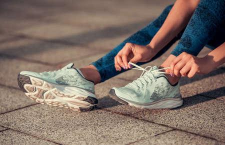 Bebouwd beeld van mooi Afro Amerikaans meisje in sportkleding die loopschoenen rijgen tijdens ochtendlooppas Stockfoto