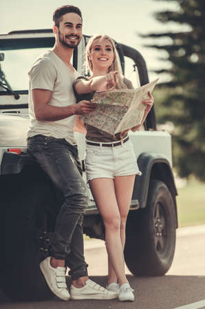Full length portrait of couple studying map and surroundings and smiling while standing near car during travel