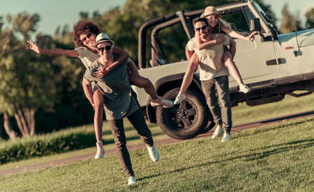 the jeep: Happy young couples are walking and smiling while travelling by car in sunny weather, girls are sitting pickaback