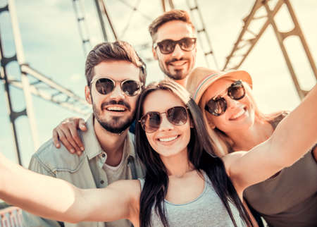 Cheerful young people are doing selfie, looking at camera and smiling while walking outdoors