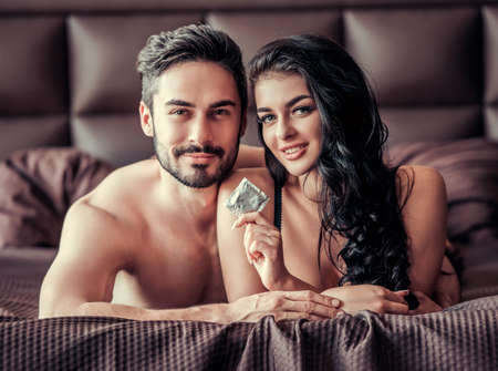 Sexy young couple is looking at camera and smiling while lying on bed at home, woman is holding a condom