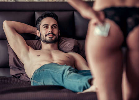 Couple having intimate moment. Handsome man is lying on bed and looking at sexy woman in black panties holding a condom