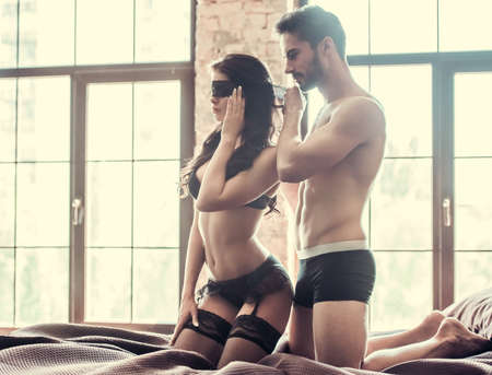 Young couple is having intimate moment. Handsome man is putting black bandage on woman's eyes photo
