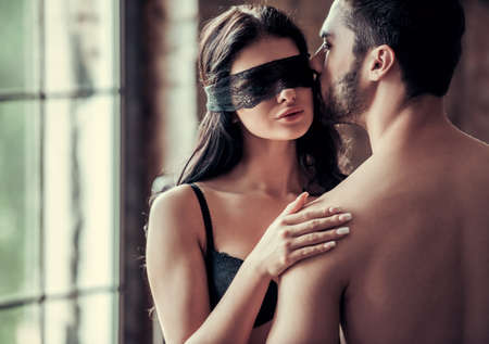 Young couple is kissing and hugging before having intimate moment. Beautiful woman with a black bandage on her eyes photo