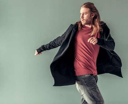 어깨 길이의 금발 머리와 캐주얼 옷 세련된 젊은이는 회색 배경에 세련된 후드 가디건에 포즈입니다