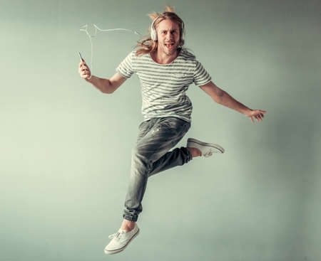 Stylish young man with shoulder-length blond hair and in headphones is listening to music while jumping, on gray background