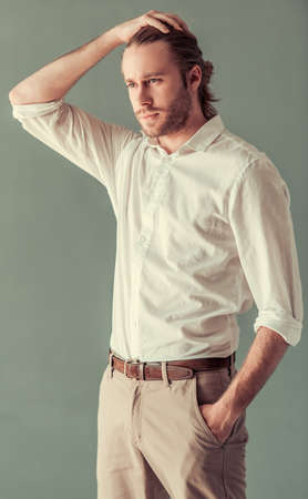 Stylish young businessman with shoulder-length blond hair and in smart casual suit is smoothing hair, on gray background
