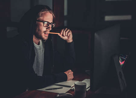 Handsome young man in hoodie and eyeglasses is chewing a pencil while working with a computer at night