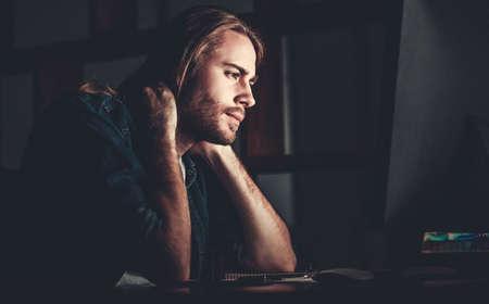 Knappe jonge zakenman met schouderlengte blond haar werkt 's nachts aan een computer