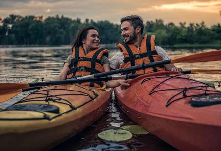 항해 카약 동안 바다 조끼에 행복 젊은 부부는 웃고있다