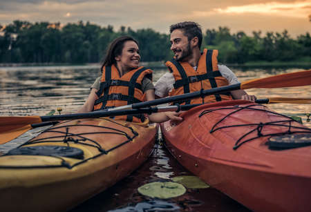 Happy young couple in sea vests is smiling while sailing kayaks Banco de Imagens