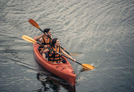 Happy young couple in sea vests is smiling while sailing a kayak
