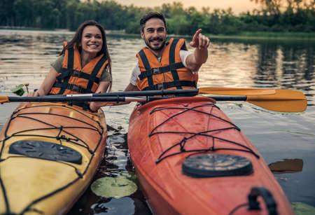 Happy young couple in sea vests is smiling while sailing kayaks Stock Photo