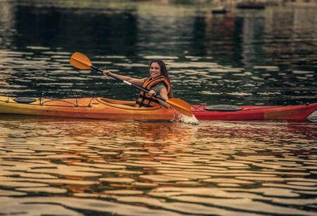 海のベストの美しい若い女性はカヤックを航行しながら笑っています。 写真素材 - 83936519
