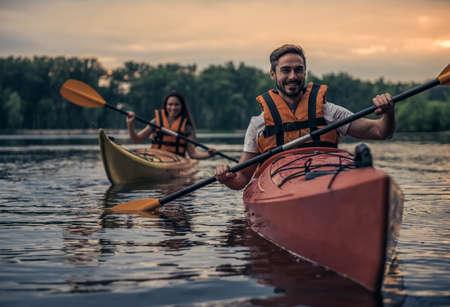 Felice giovane coppia in dune di mare sta sorridendo mentre kayak kayak