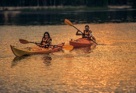 海ベストで幸せな若いカップルはカヤックを航行しながら笑っています。 写真素材