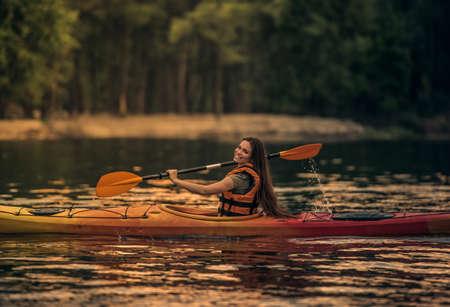 海のベストの美しい若い女性はカヤックを航行しながら笑っています。 写真素材 - 83936550