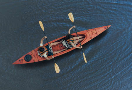 Top view of happy young couple in sea vests sailing a kayak Banco de Imagens