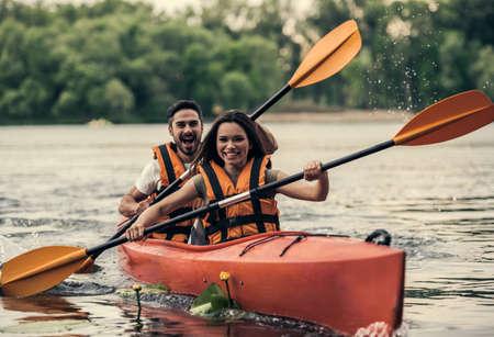 바다 조끼에 행복 한 젊은 커플 카약 항해하는 동안 웃 고있다