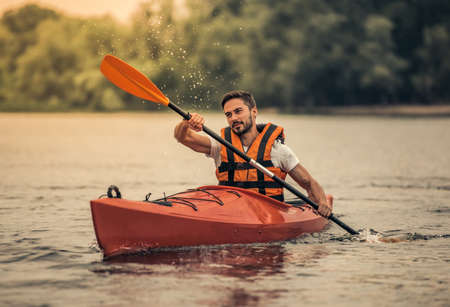 Handsome young man in sea vest is smiling while sailing a kayak