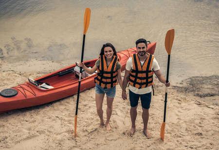 海ベストで幸せな若いカップルのパドルを保持、カメラ目線、川でカヤックの近くに立っている間笑顔