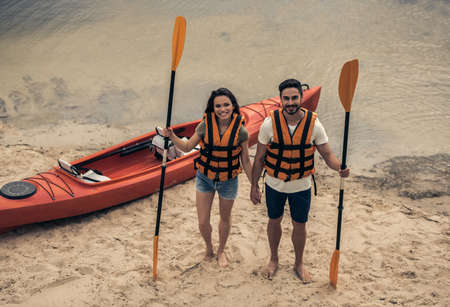 Happy young couple in sea vests is holding paddles, looking at camera and smiling while standing near the kayak at the river