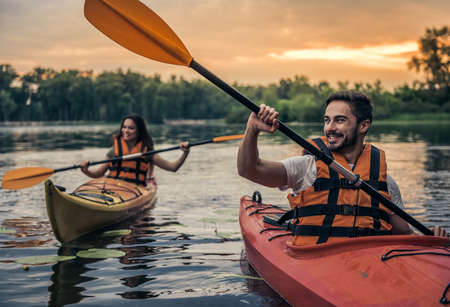 Happy young couple in sea vests is smiling while sailing kayaks Stockfoto