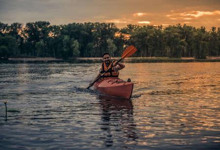 海ベストでハンサムな若い男はカヤックを航行しながら笑っています。